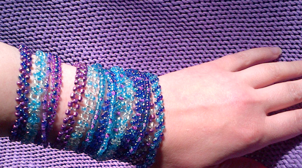 forearm almost covered with a series of bead bracelets in purple, turquoise and silver colours